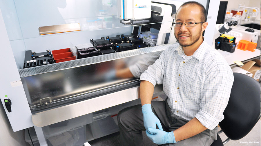 A man wearing blue protective gloves with his shirt sleeves rolled up sits next to high-tech lab equipment. A microscope is in the background.